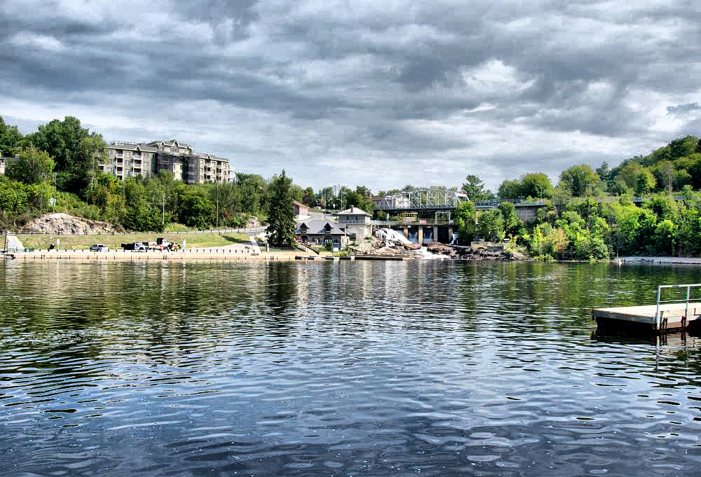 A view of the lake in Bracebridge park showing a condo building on the left, and the power station at the end.