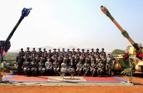 Image Attribute: India's Defence Minister Nirmala Sitharaman and Chief of the Army Chief (COAS) General Bipin Rawat and others pose for a group photograph at the formal induction of three major artillery gun systems including the M777 American Ultra Light Howitzers and the K-9 Vajra into the Army during a ceremony at Deolali artillery centre in Nashik district Friday November 9, 2018. / Source: Press Trust of India (PTI)