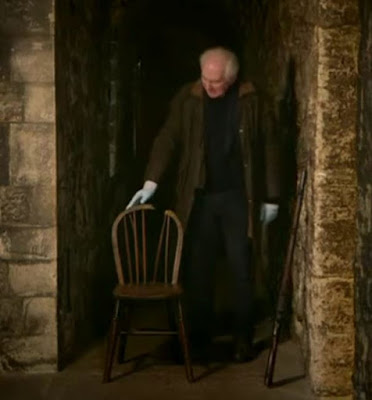Screenshot of Dan Cruickshank with the chair upon which Josef Jakobs faced the firing squad on 15 August 1941. - Majesty & Mortar: Britain's Great Palaces - Opening the Palace Doors