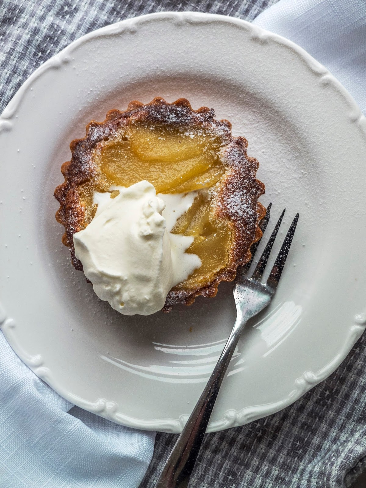 Food photo of a pear tart on a white plate and white cloth.