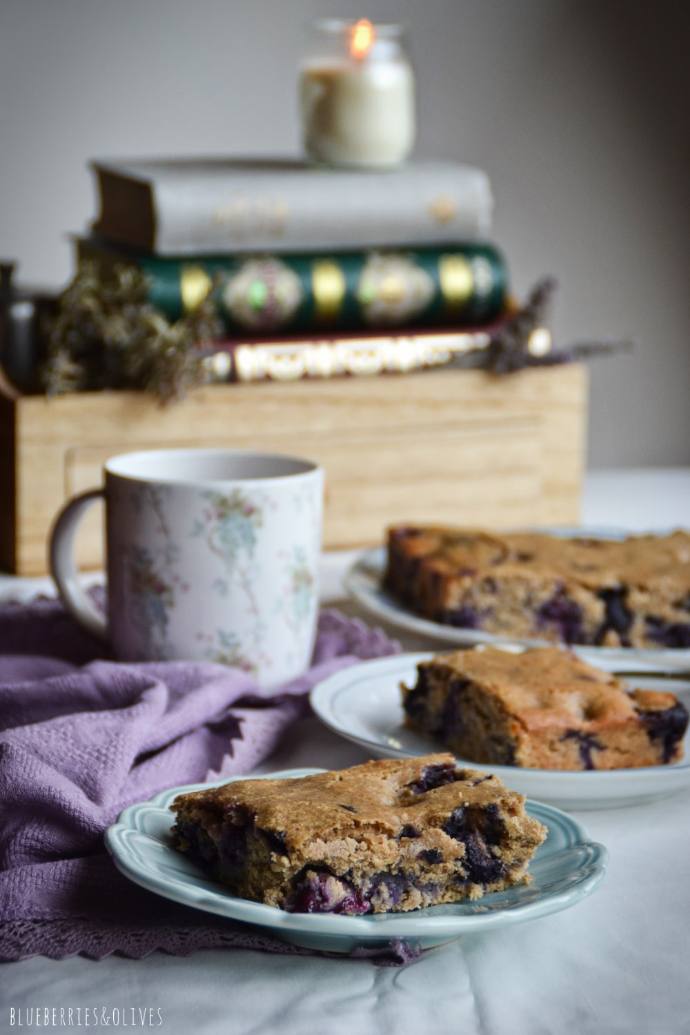 PIECES OF BLUEBERRY CAKE IN SMALL DISHES, LAVENDER FLOWERS, OLD RECIPE PAPER, BLACK TEA ON MUG
