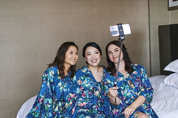 Vancouver beauty, life and style blogger Solo Lisa and her bridesmaids take a selfie with a selfie stick while getting ready, wearing Smash + Tess kimonette robes in a blue pattern.