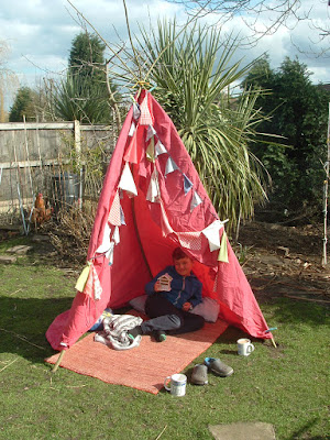 In a garden, a boy reclining under a tent made from a sheet decorated with bunting
