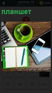 На столе лежат блокнот, чашка и планшет с телефоном. рядом расположен ноутбук для работы