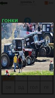 На старте стоят несколько тракторов готовые к гонкам, водители рядом