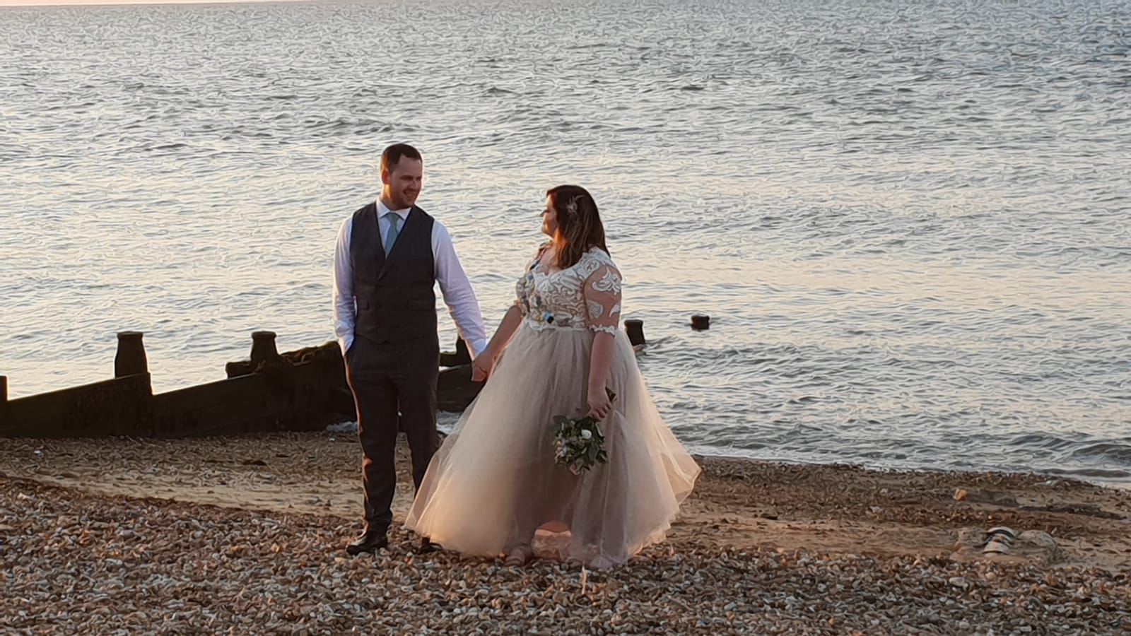 A bride and groom walk on the beach