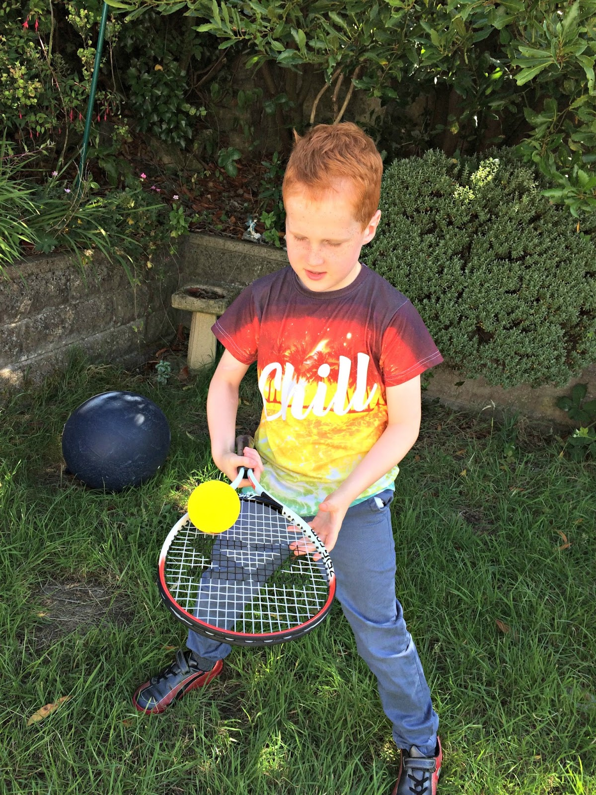 Ieuan balancing a tennis ball on a tennis racquet
