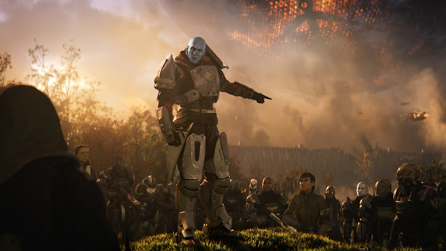 A man with blue skin and heavy metal armour addresses a crowd of soilders atop a grassy knoll, from Destiny 2
