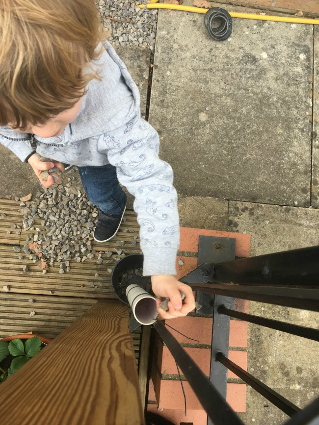 5-minute-games-for-toddlers-down-the-drain-pipe-image-of-toddler-putting-stones-down-pipe