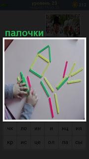 за столом ребенок занимается с цветными палочками