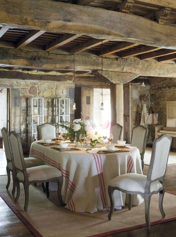 Rustic elegant #Frenchfarmhouse dining room with rough hewn beams and red stripe tablecloth