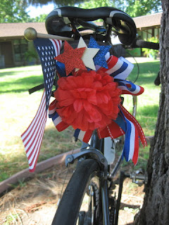 Bicycle saddle decorated with an American Flag and red, white, and blue ribbon, San Jose, California