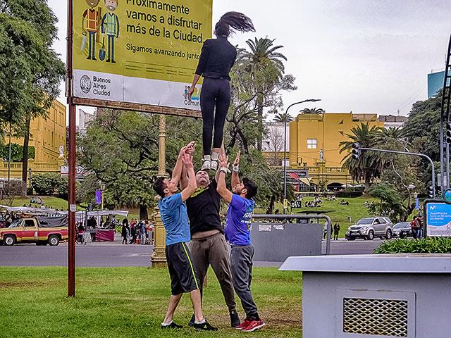 Grupo de jóvenes arrojando por el aire a una muchacha.