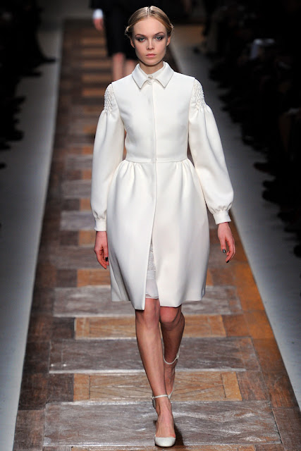 model from valentino fall 2012 runway show wearing a white winter coat over a white dress