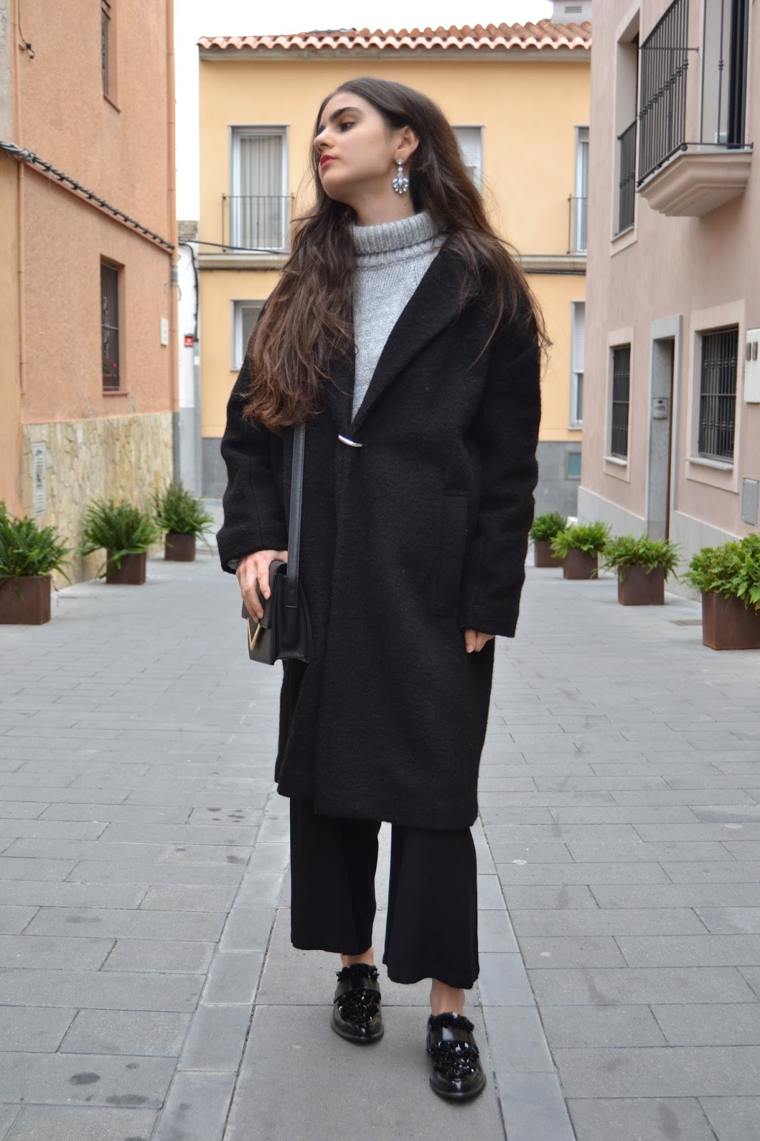 black oversized coat and earrings