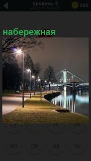 Тропинка вдоль реки, набережная ведет к мосту и фонари вдоль всей улицы