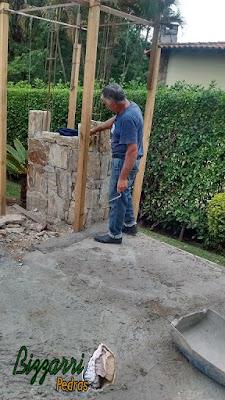 Bizzarri, da Bizzarri Pedras, fazendo a parede de pedra com pedra madeira onde vamos colocar o forno de pizza com a execução do pergolado de madeira com cobertura de policarbonato em residência em condomínio em Vinhedo-SP.
