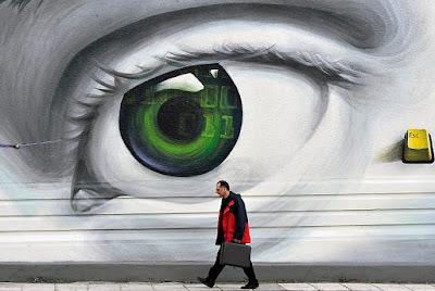 """Un informaticien marche sous une affiche représentant un œil qui l'observe et une touche de clavier """"Escape"""""""