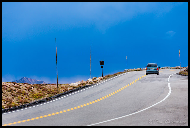 A minivan drives up Trail Ridge Road as storm clouds begin form over the mountains.