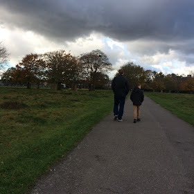 Father and son walk along a path with dark clouds overhead