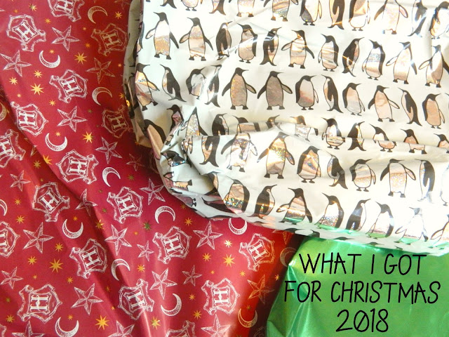 A photograph showing Christmas wrapping paper, one with penguins, one with Harry Potter themed print, one shiny green one