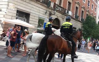 Dos policías a caballo recorren la calle.