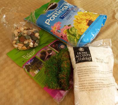 Potting soil, rocks, moss, and decorative snow