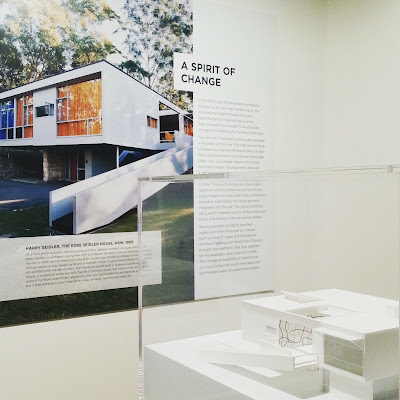 Architect's model of a modernist building in a perspex case in front of a large photo and information about it on the wall behind.