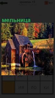 Стоит деревянная мельница с колесом около воды и работает