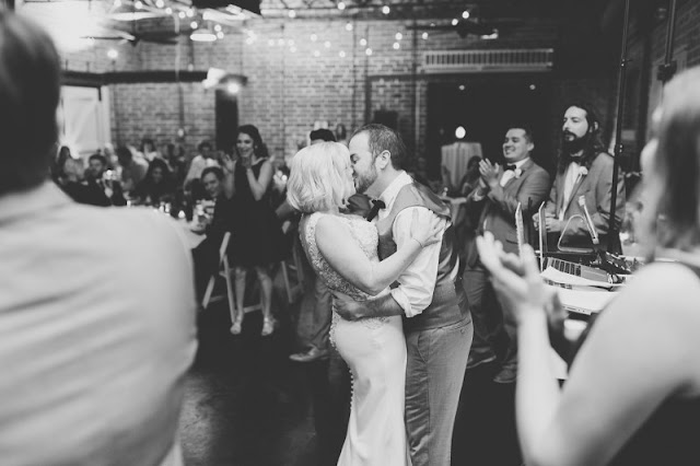 bride and groom kiss on dance floor-black and white