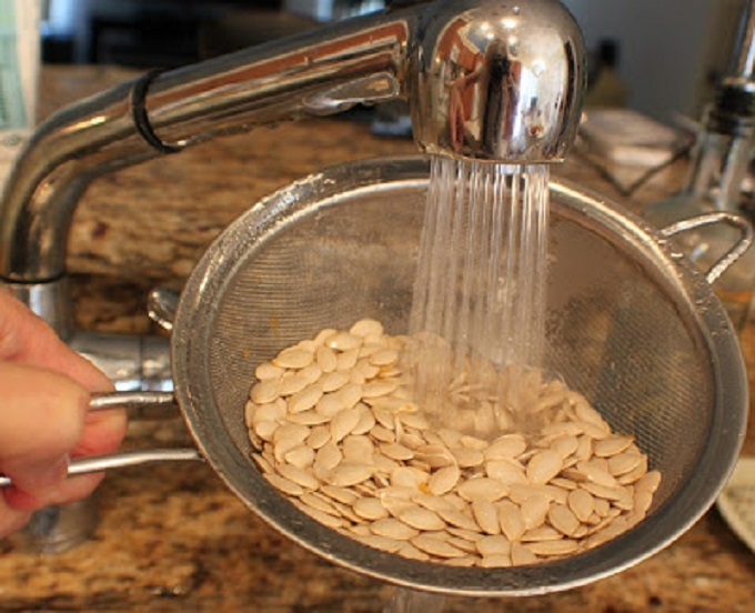 These are pumpkin seeds that were raw being washed off from a carved pumpkin and then roasted with Italian seasoning. This is how to roast pumpkin seeds and make them from scratch by using a sugar pie pumpkin after carving from Halloween. These pumpkin seeds are in a white round bowl and have a crispy outside shell and ready to snack on.