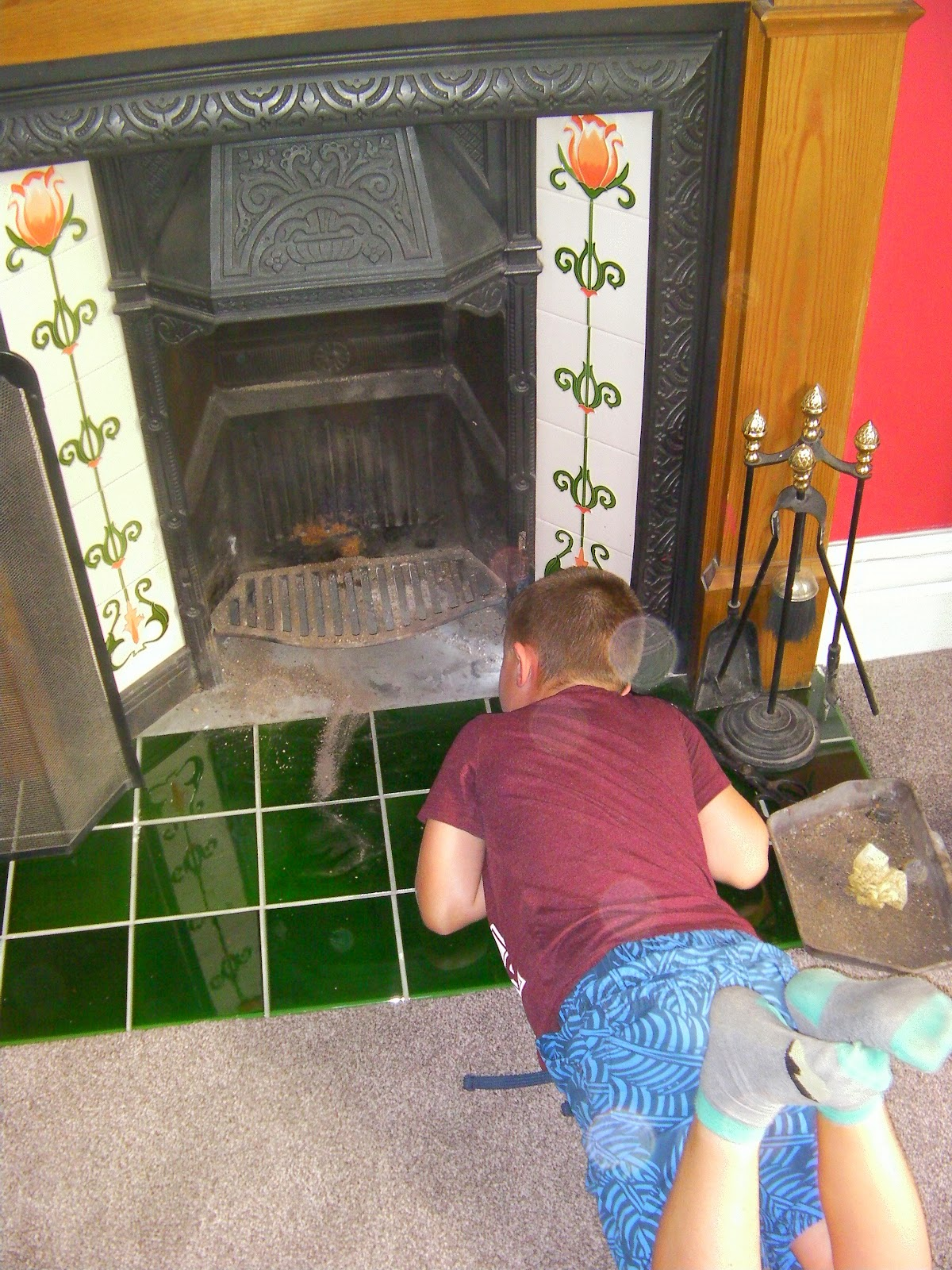 boy hunting mice behind the fireplace