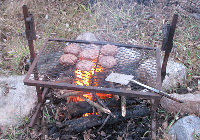 hamburgers on a grill over an open fire