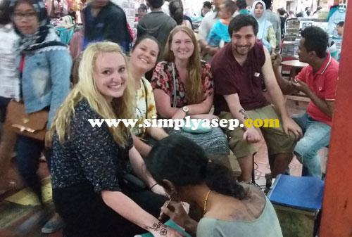 BULE : Sekelompok turis asing sedang dirias tato nya di areal kawasan Malioboro (25/7).  Ada yang kenal dengan mereka?  Foto Asep Haryono