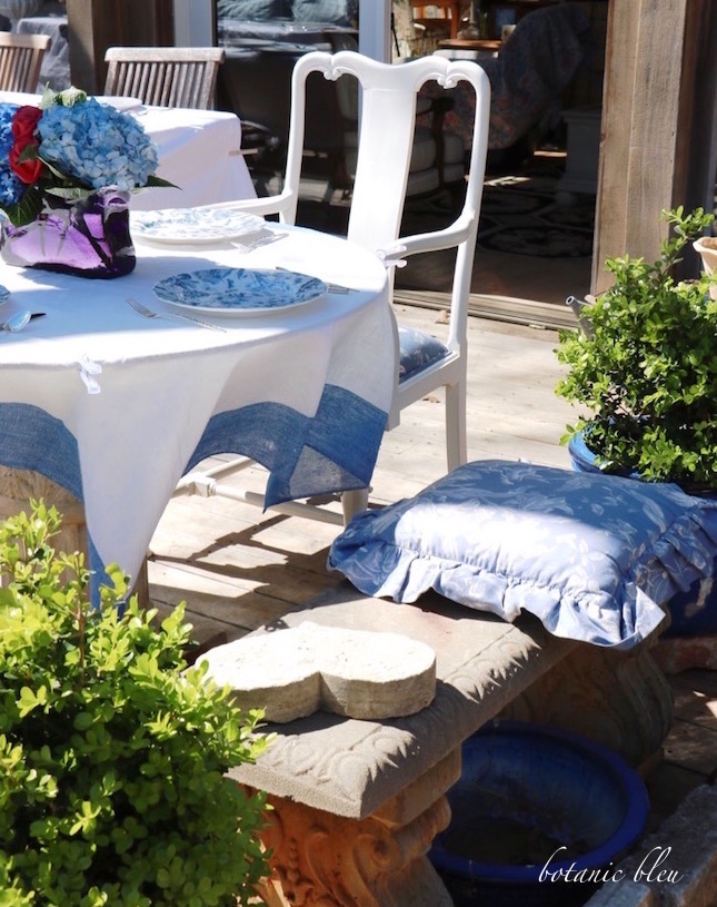 blue-white-cushion-on-concrete-bench-as-seat-to-garden-party-table