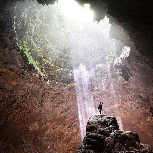 Tinuku Travel Jomblang cave in Gunung Kidul karst bring heaven light and perpetuate ancient forest in bottom earth