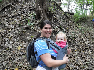 woman with baby in carrier smiling next to large tree and fall leaves at Ravine Park in Sioux City, Iowa