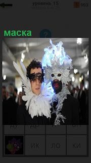 Двое мужчин в помещении одели маски на лица белого цвета