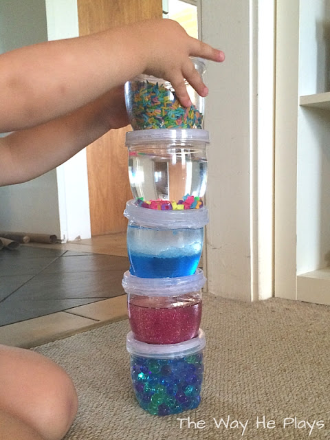 Toddler stacking the discovery jars