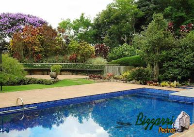 Construção da piscina em condomínio em Atibaia com a construção da residência com os caminhos de pedra com o banco de madeira.