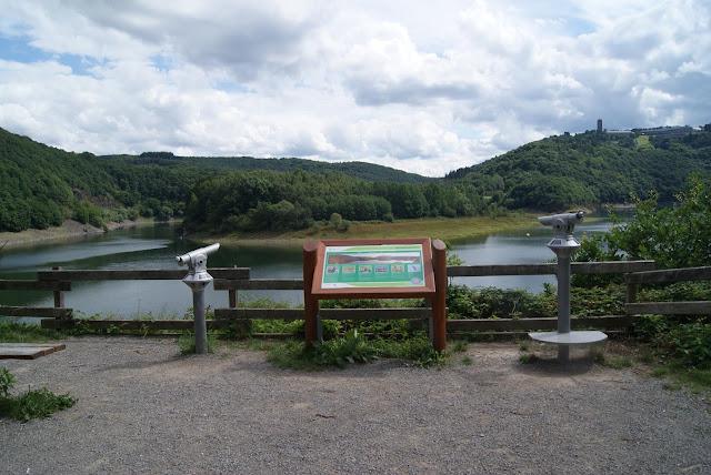 Auf einem Platz steht ein Schild, daneben zwei Fernrohre. Im Hintergrund liegt der See und viel Wald.