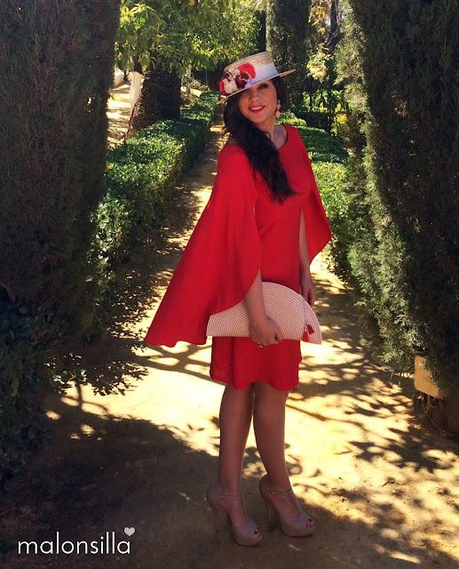 Invitada con vestido rojo posando en unos jardines de Sevilla