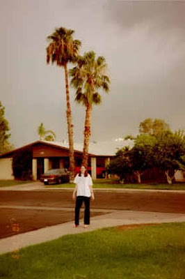 Me standing on the suburban street outside of my host family's house with grey clouds and palm trees in the background