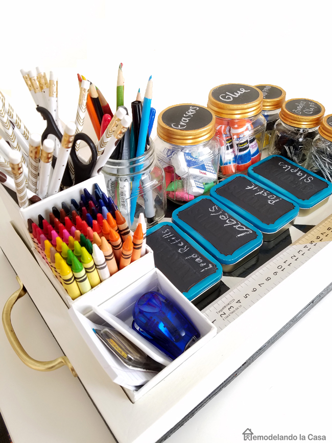 crayons, stapler, white black and golden pencils, Altoids containers storing school supplies