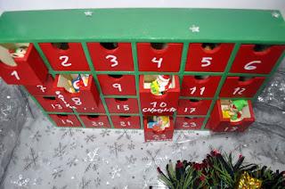rojo y verde, números en blanco, se ven figuras navideñas en los cajones