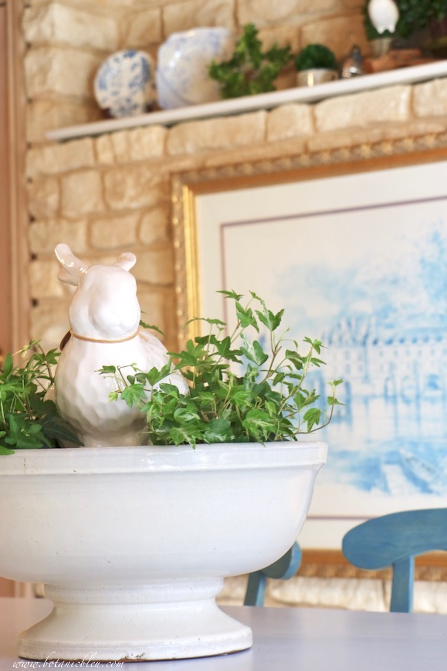 Large white rabbit sits in a botanical centerpiece in a French Country kitchen