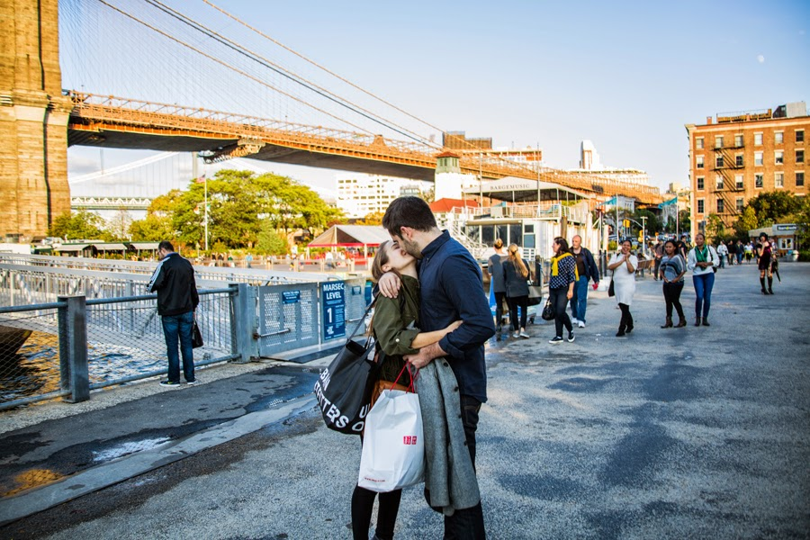 Newly engaged couple kissing in DUMBO Brooklyn Bridge Park - www.cassiecastellaw.com