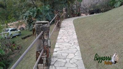 Caminhos com pedras caco de São Tomé com o corrimão de ferro preso nos pilares de pedra em sítio em Atibaia-SP.