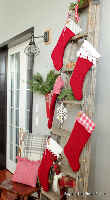 wrap fairy lights around an old ladder for a stocking hanger
