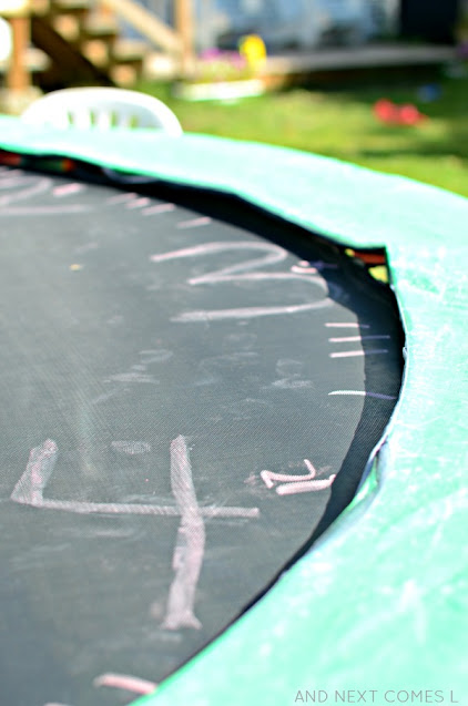 Close up of sidewalk chalk clock on a trampoline as part of a telling the time activity for kids